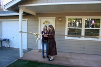 Family cutting their ribbon on the day of their home dedication ceremony